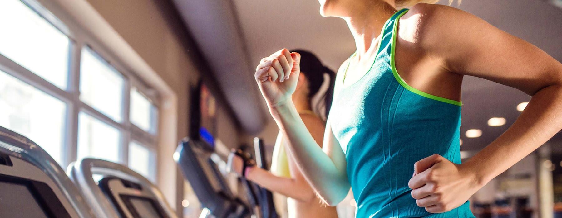 people running on treadmills in bright fitness center