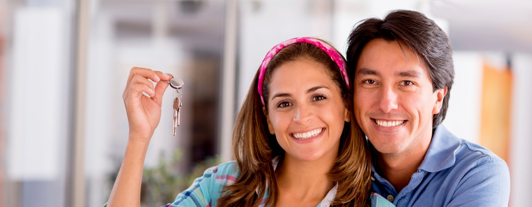 smiling couple pose for the camera with their apartment keys