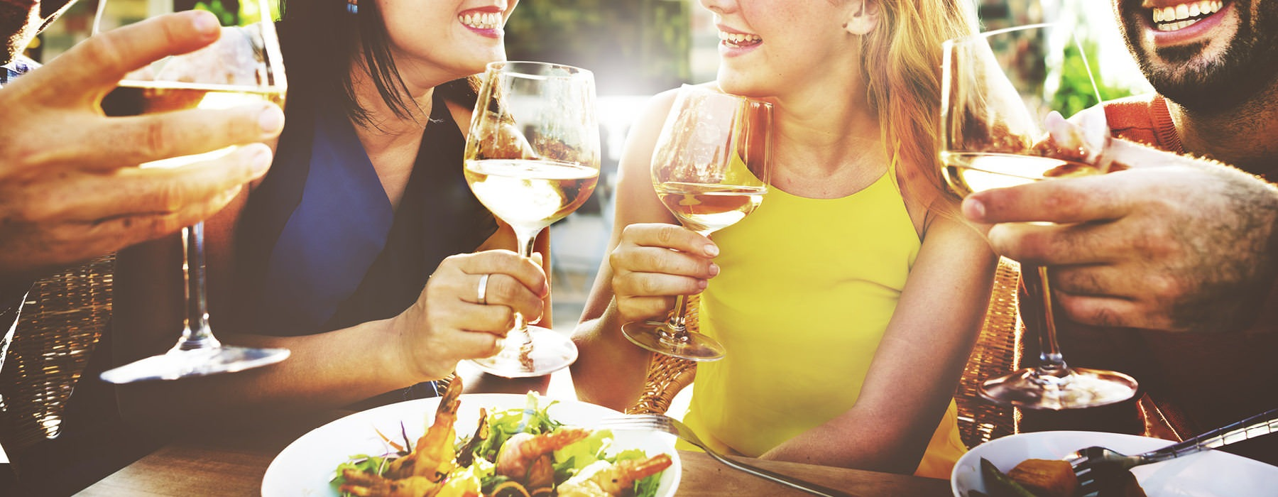 20 somethings toast wine glasses around a restaurant's table outdoors