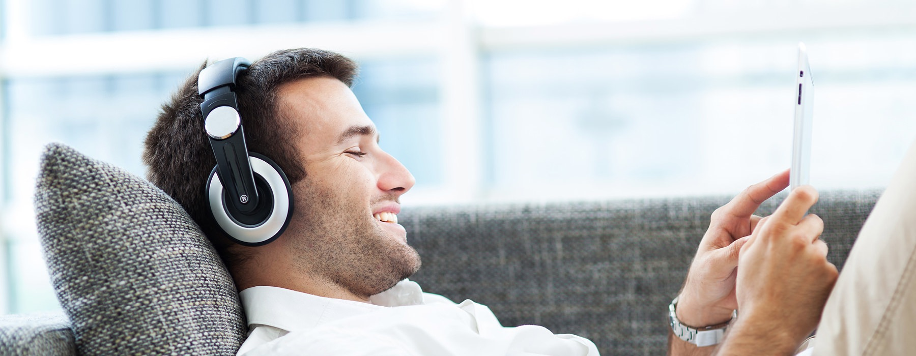 man with headphones on lays on sofa as he smiles at the device pad in his hands